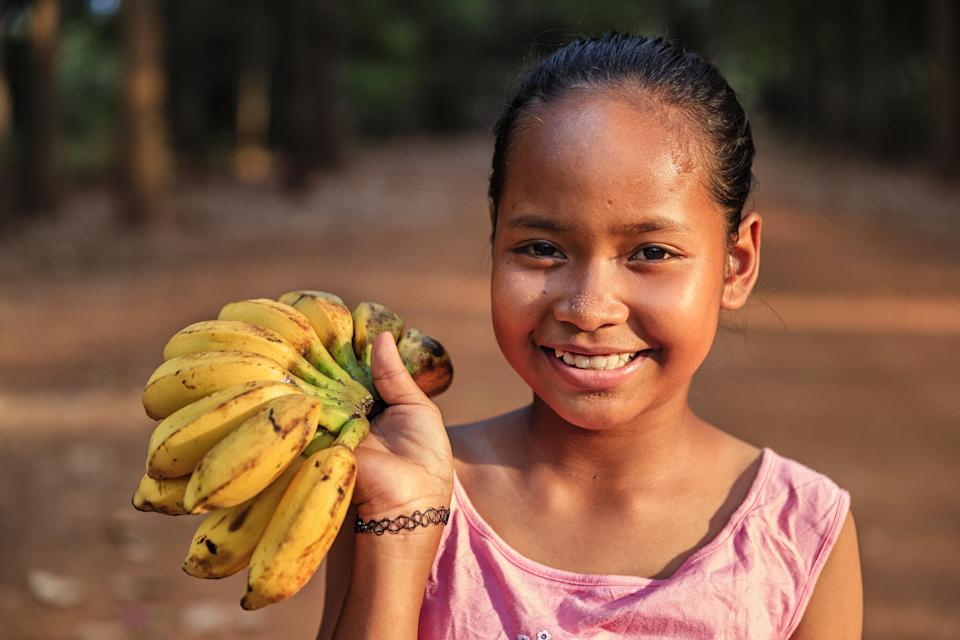 A young Cambodian girl smiles as she sells fresh bananas in a village close to Siem Reap, Cambodia