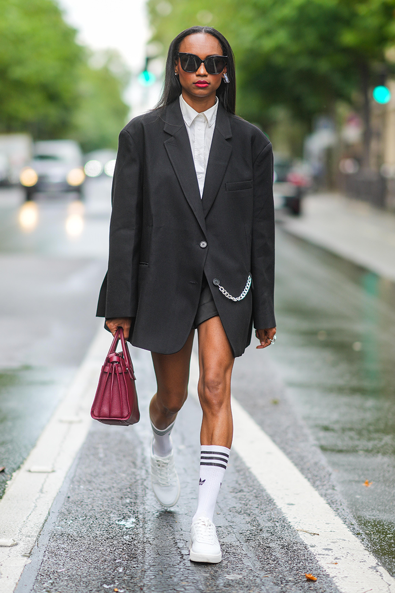 """<p>Lean into the oversized blazer trend by wearing over a buttoned-up shirt and teaming with casual <a href=""""https://www.cosmopolitan.com/uk/fashion/style/a27431191/womens-white-trainers/"""" rel=""""nofollow noopener"""" target=""""_blank"""" data-ylk=""""slk:white trainers"""" class=""""link rapid-noclick-resp"""">white trainers</a> and skater socks for a sporty spin on the summer suit. </p>"""