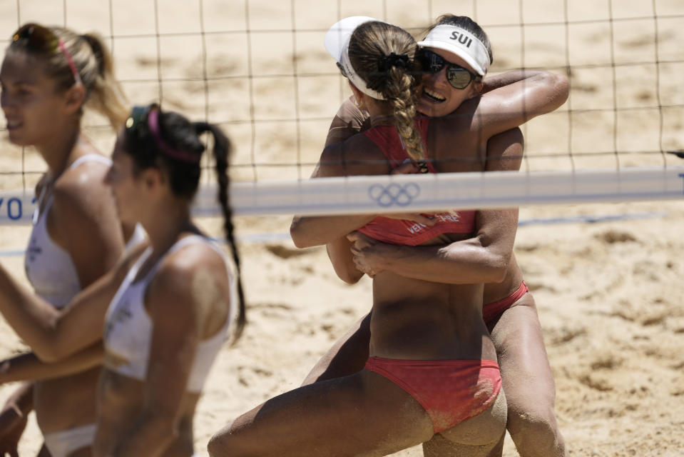 Anouk Verge-Depre, second from right, of Switzerland, hugs teammate Joana Heidrich as they celebrate winning a women's beach volleyball Bronze match against Latvia at the 2020 Summer Olympics, Friday, Aug. 6, 2021, in Tokyo, Japan. (AP Photo/Petros Giannakouris)