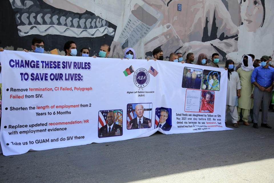 FILE - In this June 25, 2021, file photo, former Afghan interpreters hold placards during a demonstrations against the US government, in front of the US Embassy in Kabul, Afghanistan. The House voted overwhelmingly Thursday, July 22, to allow in thousands more of the Afghans who worked alongside Americans in the Afghanistan war, citing the urgency of protecting those on-the-ground allies from Taliban retaliation as the U.S. military withdrawal enters its final weeks. (AP Photo/Mariam Zuhaib, File)