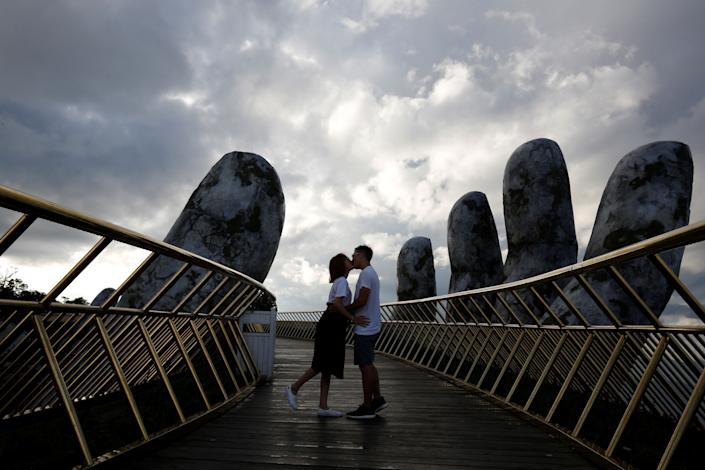 A young couple kisses near the giant hands.