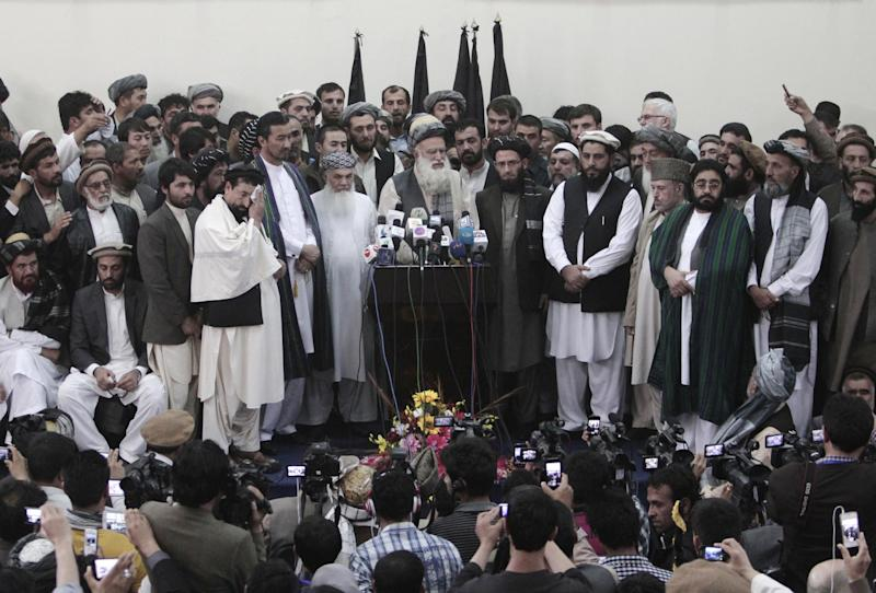 Abdul Rab Rasoul Sayyaf, an influential lawmaker and religious scholar, at podium, speaks during a press conference after registering his candidacy in next year's presidential election in Kabul, Afghanistan, Thursday, Oct. 3, 2013. Another former warlord, Ismail Khan, who formerly served as energy and water minister, said he will run for Sayyaf's first vice-president in the April 5 vote. (AP Photo/Rahmat Gul)