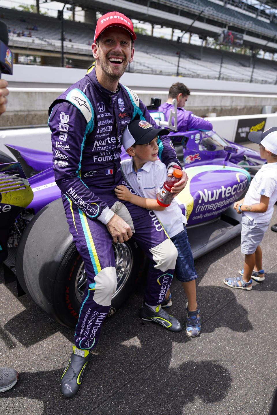 Romain Grosjean, of Switzerland, hugs his son Sacha after finishing second in the IndyCar auto race at Indianapolis Motor Speedway in Indianapolis, Saturday, Aug. 14, 2021. (AP Photo/Michael Conroy)