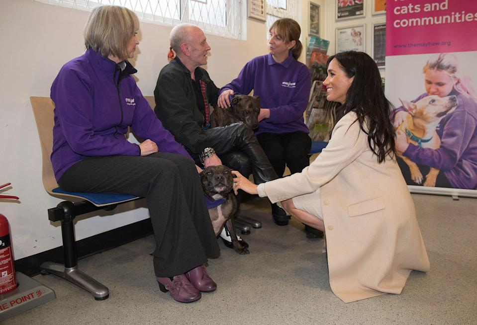 The Duchess of Sussex meets Wully Struthers and his staffies Azzy and Gallis during a visit to animal welfare charity Mayhew (PA Archive)