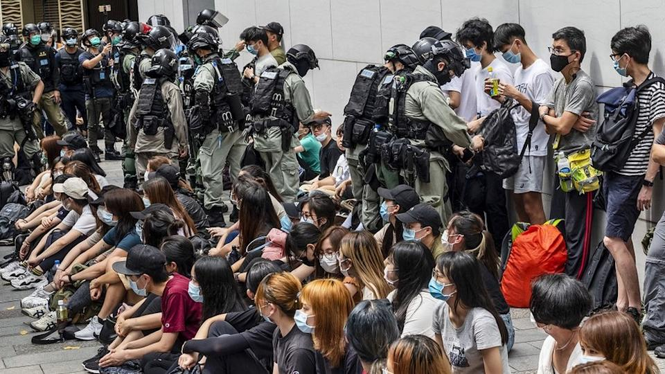 """Police officers opening detainees"""" bags and checking on their smartphones as police has set up a police cordon around the area in Causeway Bay, Hong Kong, China, 27 May 2020. The Second Reading debate on the National Anthem Bill is set to resume at the Legislative Council on 27 May amid growing anger at Beijing""""s plan to impose a national security law on the city banning sedition, secession and subversion through a method that could bypass Hong Kong""""s legislature."""