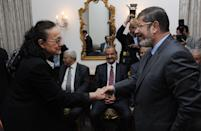 In this photo released by Middle East News Agency, the Egyptian official news agency, President-elect Mohammed Morsi, right, shakes hands with a woman, name not given, in Cairo, Egypt, Monday, June 27, 2012. Now that Egypt has its first freely elected civilian president, the still-dominant military may be seeking to emulate the Turkish model a mostly Muslim nation with a history of military rule and democratic evolution. (AP Photo/Mohammed Abd El-Maaty, Middle East News Agency, HO)