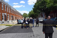 Baltimore Police Commissioner Michael Harrison, center, Baltimore Mayor Brandon Scott, second from right, confer at the scene of a shooting, Wednesday, June 16, 2021, in Baltimore. One person was killed and five others were wounded Wednesday when gunmen walked up a street and opened fire on a Baltimore block from an intersection, the city's police commissioner said. (Kim Hairston/The Baltimore Sun via AP)