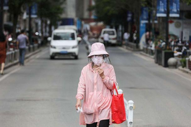 PHOTO: A woman wears a face shield as she walks along a street in Wuhan in China's central Hubei province on May 11, 2020. (AFP via Getty Images)