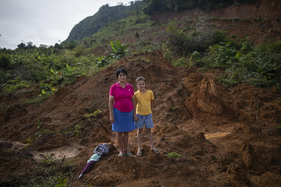 Martina Caballero, 63, stands for a portrait with her with her granddaughter, Heydi Rivera Caballero, 10, at the site of their home which was destroyed by a landslide triggered by hurricanes Eta and Iota in the village of La Reina, Honduras, Thursday, June 24, 2021. Home to about 1,000 people, the town in western Honduras was hit by two powerful hurricanes within three weeks, natural disasters made far worse by local deforestation and climate change. La Reina was buried by a landslide. (AP Photo/Rodrigo Abd)