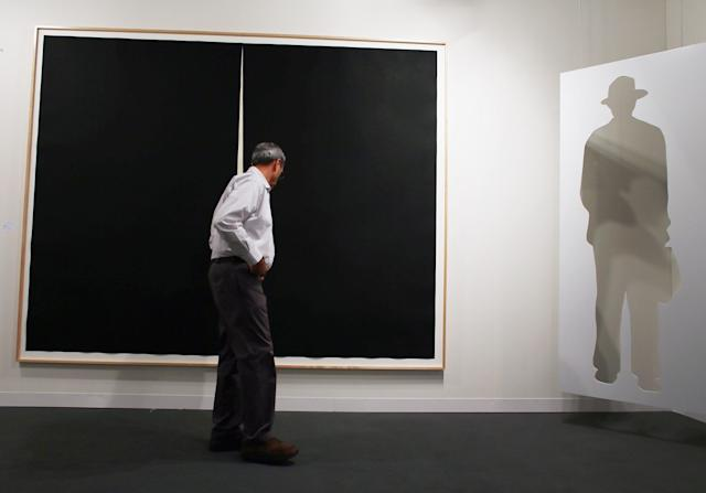 MIAMI BEACH, FL - DECEMBER 05: An art patron looks at the art on the walls of the Gemini GEL gallery as Art Basel opens at the Miami Beach Convention Center on December 5, 2012 in Miami Beach, Florida. The 11th edition of the art show runs from December 6 through the 9th. (Photo by Joe Raedle/Getty Images)
