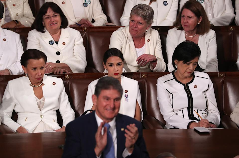 Democratic women of the U.S. House of Representatives, including Rep. Alexandria Ocasio-Cortez (D-NY) (C), remain in their seats as Senator Joe Manchin (D-WV) stands and applauds in front of them as U.S. President Donald Trump delivers his second State of the Union address to a joint session of Congress at the U.S. Capitol in Washington, U.S. February 5, 2019. REUTERS/Jonathan Ernst