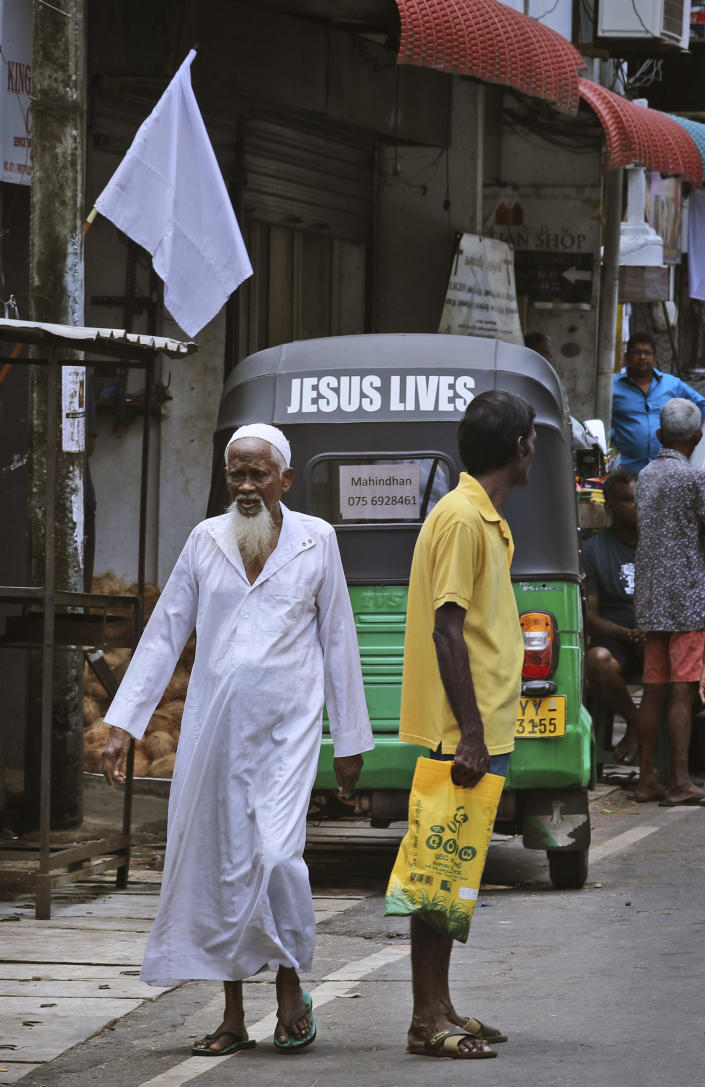 """An elderly Sri Lankan Muslim man walks across a street in Colombo, Sri Lanka, Monday, April 29, 2019. The Catholic Church in Sri Lanka said Monday that the government should crack down on Islamic extremists with more vigor """"as if on war footing"""" in the aftermath of the Easter bombings. Meanwhile, the government has banned all kinds of face coverings that may conceal people's identities. The emergency law, which took effect Monday, prevents Muslim women from veiling their faces. (AP Photo/Manish Swarup)"""