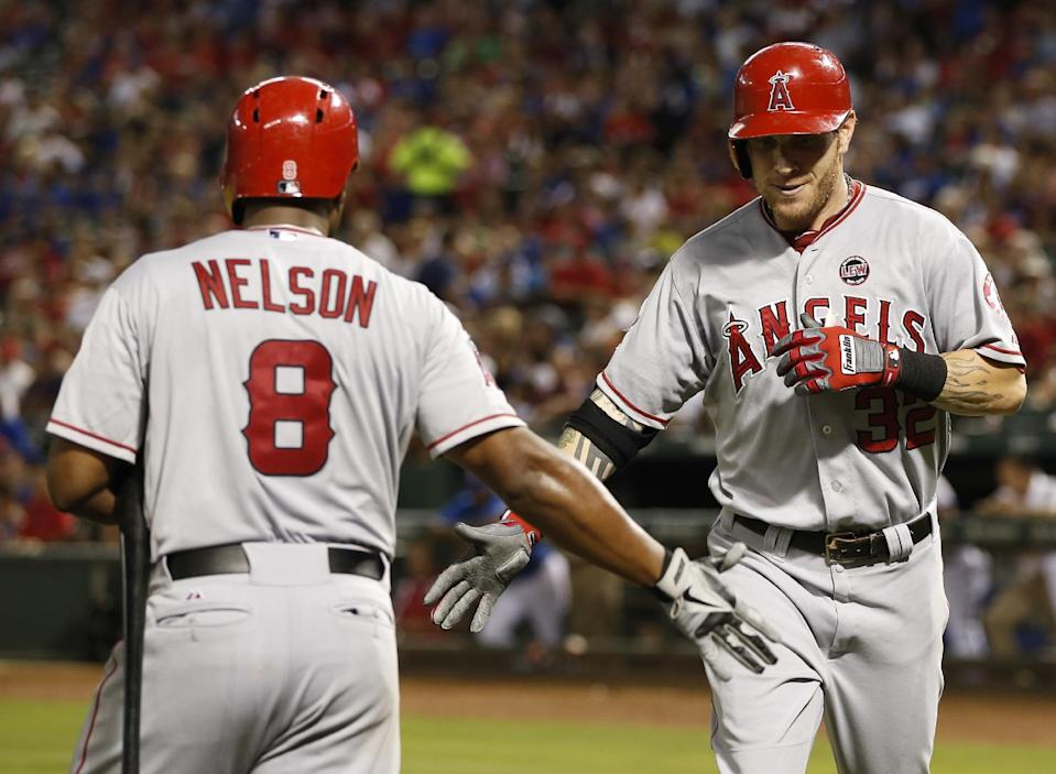 Los Angeles Angels' Josh Hamilton, right, is greeted by Chris Nelson (8) after hitting a solo home-run against the Texas Rangers during the seventh inning of a baseball game, Wednesday, July 31, 2013, in Arlington, Texas. (AP Photo/Jim Cowsert)