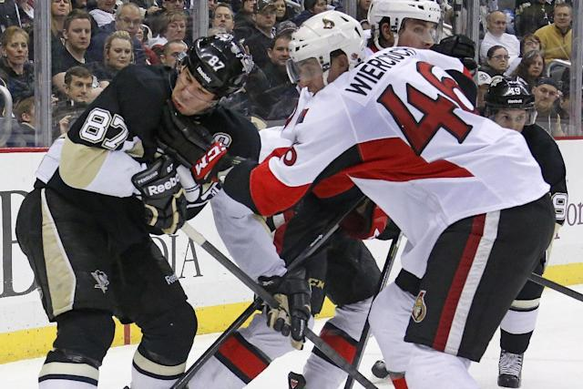 Ottawa Senators' Patrick Wiercioch (46) gets his glove in the face of Pittsburgh Penguins' Sidney Crosby (87) in the second period of an NHL hockey game in Pittsburgh, Monday, Feb. 3, 2014. (AP Photo/Gene J. Puskar)