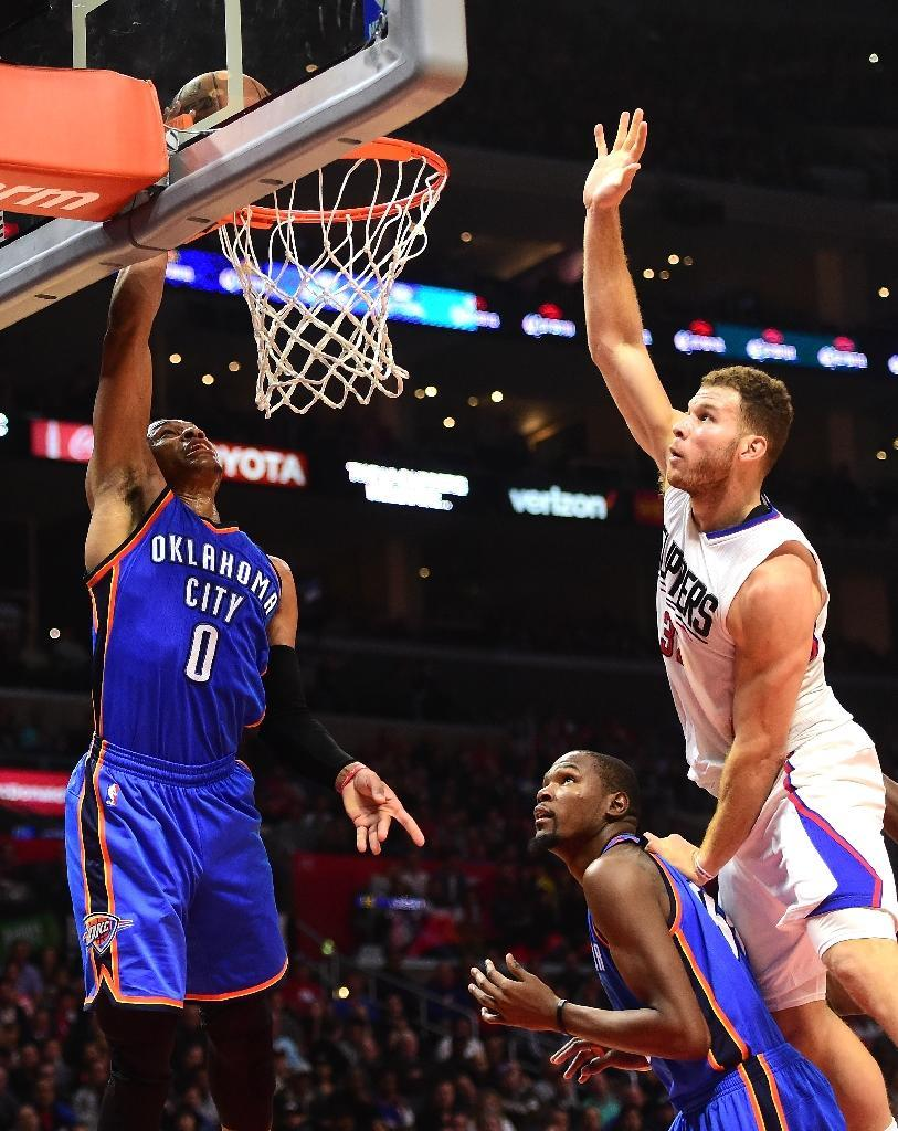 Russell Westbrook of the Oklahoma City Thunder (L) scores on a layup during the first half at Staples Center on December 21, 2015 in Los Angeles, California (AFP Photo/Harry How)