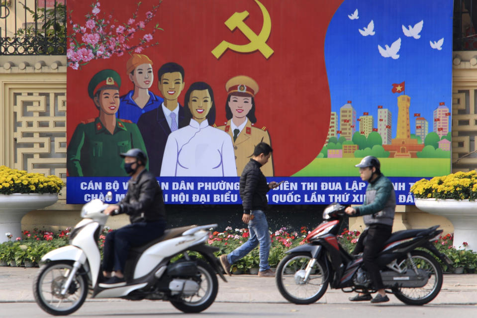 People ride motorcycles past a poster promoting the Communist Party Congress in Hanoi, Vietnam, Saturday, Jan. 23, 2021. Almost 1,600 leading members of Vietnam's Communist Party on Tuesday, Jan. 26, 2021 begin a meeting to set policy for the next five years and select the group's senior members to steer the nation. (AP Photo/Hau Dinh)