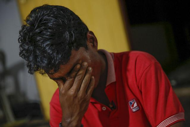 In this Nov. 23, 2013 photo, Rohingya refugee Mohamad Husein, from Myanmar, wipes tears from his eyes as he talks to reporters at his hostel on the outskirts of Alor Setar, Kedah, North Malaysia. After his tiny Muslim village in Myanmar's northwest Rakhine had been destroyed in a fire set by an angry Buddhist mob, he and his younger sister became separated from their family. (AP Photo/Vincent Thian)