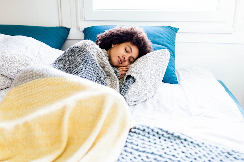 Young black woman sleeping in a bed.