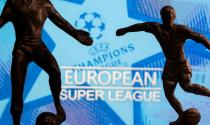 """Metal figures of football players are seen in front of the words """"European Super League"""" and the UEFA Champions League logo in this illustration"""