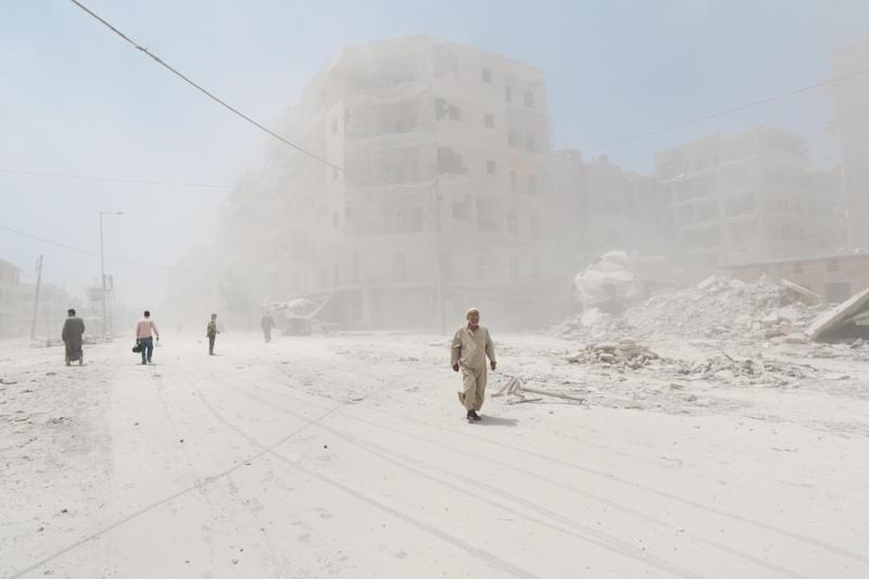 Syrians walk amid dust following a reported barrel-bomb attack by government forces on July 7, 2014 in the Tariq al-Bab neighbourhood in Aleppo (AFP Photo/Zein al-Rifai)