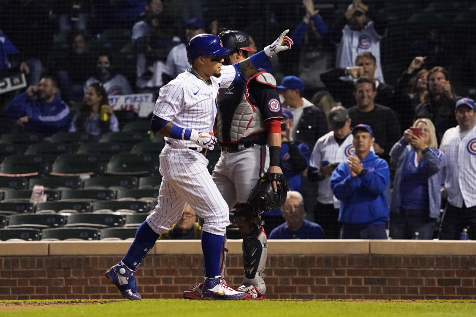 Chicago Cubs' Javier Baez (9) gestures as he crosses home plate after hitting a home run against the Washington Nationals during the sixth inning of a baseball game, Monday, May, 17, 2021, in Chicago. (AP Photo/David Banks)