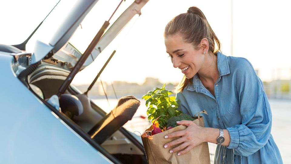 Young woman in car park carrying shopping bag of groceries.