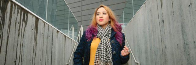hispanic woman with blonde and purple hair wearing a yellow shirt and jean jacket and scarf walking down a hall looking ahead confidently