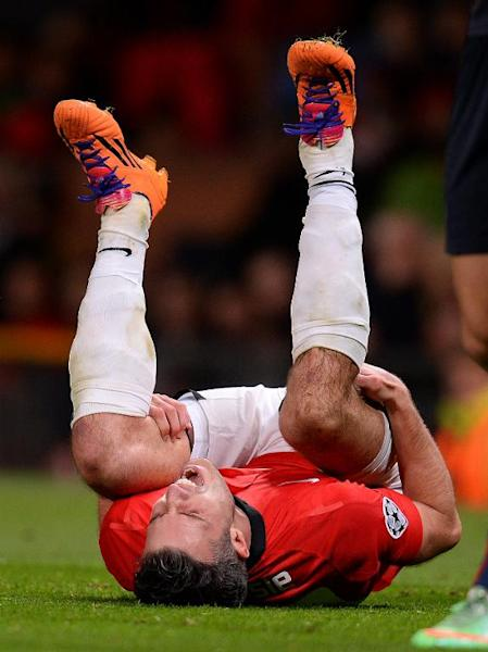 Manchester United's Robin van Persie is injured during the UEFA Champions League second leg football match between Manchester United and Olympiakos at Old Trafford in Manchester on March 19, 2014
