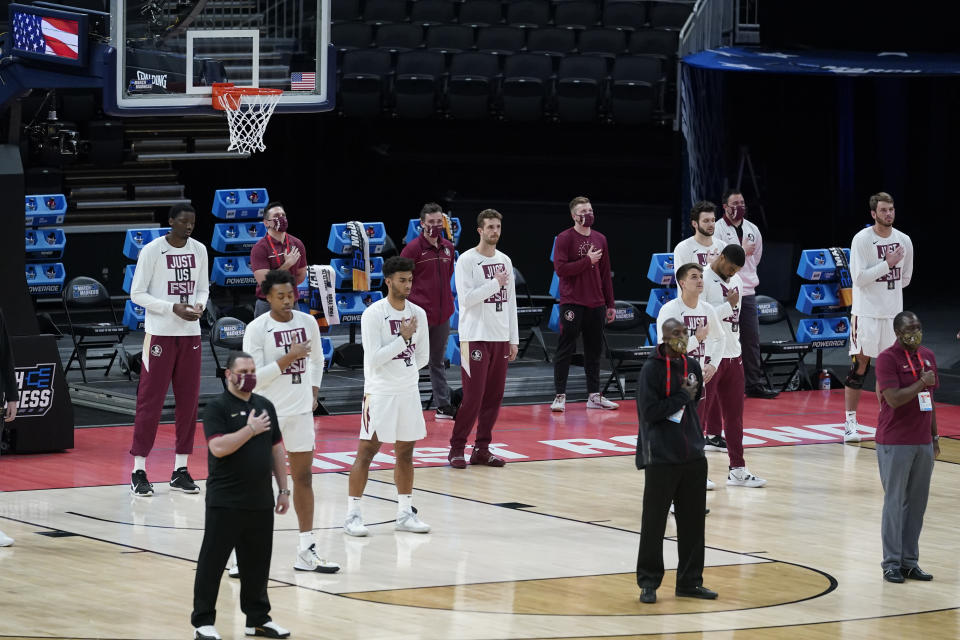 The Florida State basketball team stand socially distance during the national anthem before a first-round game against UNC-Greensboro in the NCAA men's college basketball tournament at Banker's Life Fieldhouse, Saturday, March 20, 2021, in Indianapolis. (AP Photo/Darron Cummings)