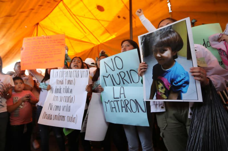 Activists hold placards at the home of Fatima Cecilia Aldrighett, 7, who went missing on February 11 and whose body was discovered over the weekend inside a plastic garbage bag, in Mexico City