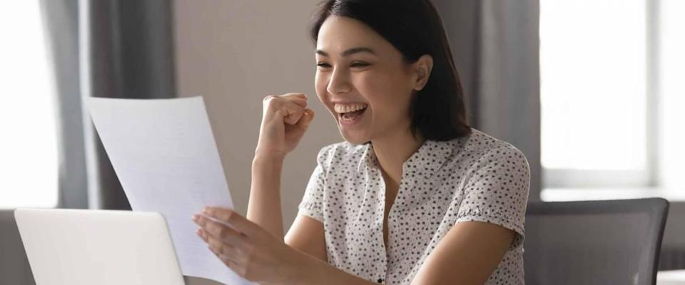 Happy woman looks at sheet of paper in front of laptop