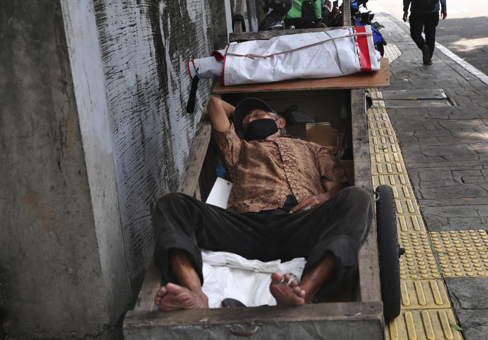 A man wearing a face mask takes a nap on his cart in Jakarta, Indonesia, Tuesday, June 22, 2021. Indonesia, the world's fourth most populous country, has seen COVID-19 infections surge in recent weeks, a climb that has been blamed on travel during last month's Eid al-Fitr holiday as well as the arrival of new virus variants, such as the the Delta version first found in India. (AP Photo/Tatan Syuflana)