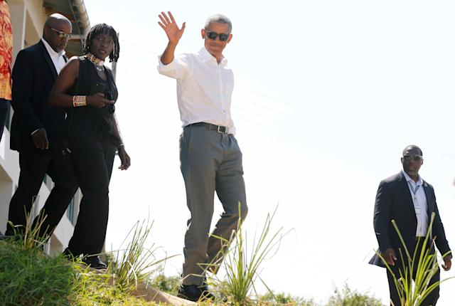 <p>Former U.S. President Barack Obama waves to photographers as he tours the Sauti Kuu resource centre near his ancestral home in Nyangoma Kogelo village in Siaya county, western Kenya July 16, 2018. With him is Auma Obama. (Photo: Thomas Mukoya/Reuters) </p>