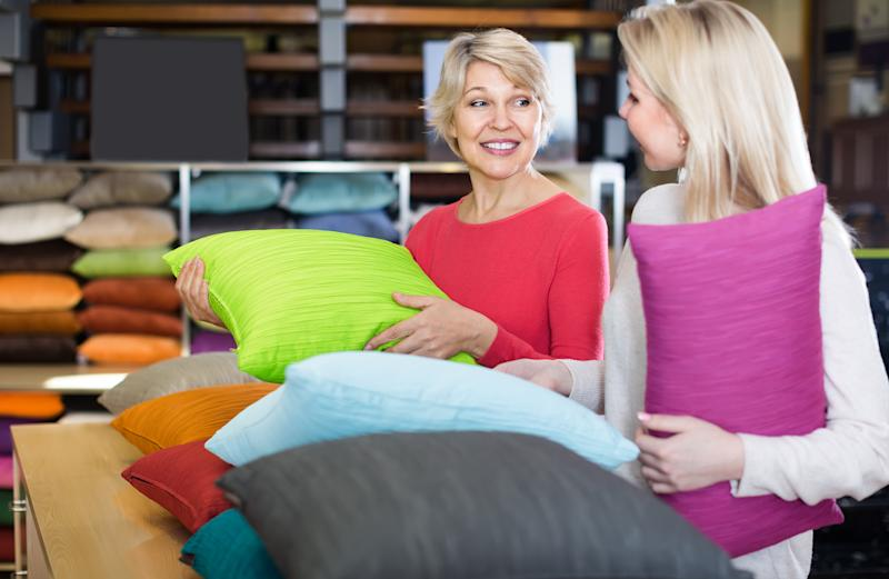 Two women shoppers looking at pillows in a store.
