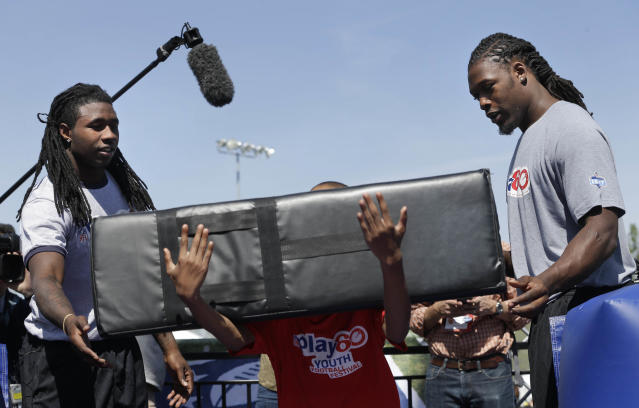 South Carolina's Jadeveon Clowney, right, and Clemson's Sammy Watkins teach tackling technique during an NFL football event in New York, Wednesday, May 7, 2014. The event was to promote Play 60, an NFL program which encourages kids to be active for a healthy life. (AP Photo/Seth Wenig)
