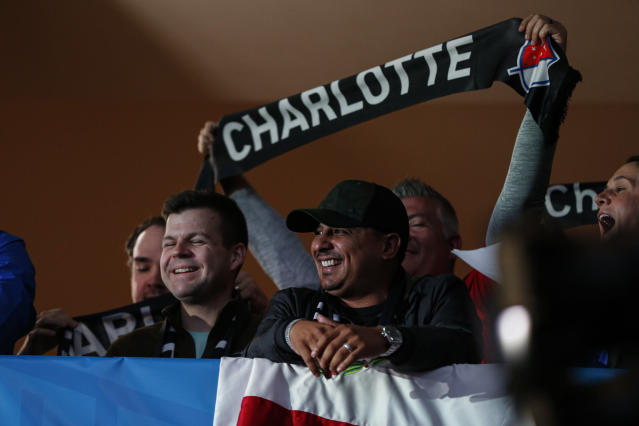 Soccer fans celebrate the announcement of a Major League Soccer team, owned by David Tepper, that will begin play Charlotte in 2021 at an event in Charlotte, N.C., Tuesday, Dec. 17, 2019. (AP Photo/Nell Redmond