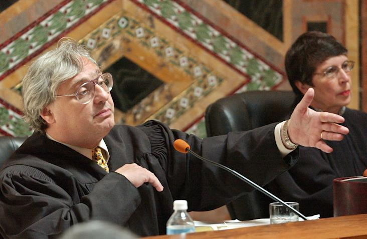 In this Sept. 22, 2003 file photo, Judge Alex Kozinski, of the 9th U.S. Circuit Court of Appeals, gestures as Chief Judge Mary Schroeder looks on in San Francisco. A decision by a divided three-judge panel of the 9th U.S. Circuit Court of Appeals in San Francisco on Wednesday, Feb. 16, 2014, reinstated a lawsuit filed against YouTube by an actress who appeared in an anti-Muslim film that sparked violence in many parts of the Middle East. The 9th Circuit said the YouTube posting infringed actress Cindy Lee Garcia's copyright to her role, and she, not just the filmmaker, could demand its removal. (AP Photo/Paul Sakuma, Pool, file)