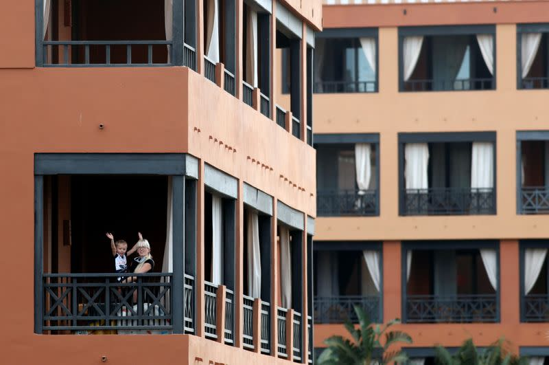 Woman plays with a child on the hotel terrace in H10 Costa Adeje Palace, which is on lockdown after novel coronavirus has been confirmed in Adeje