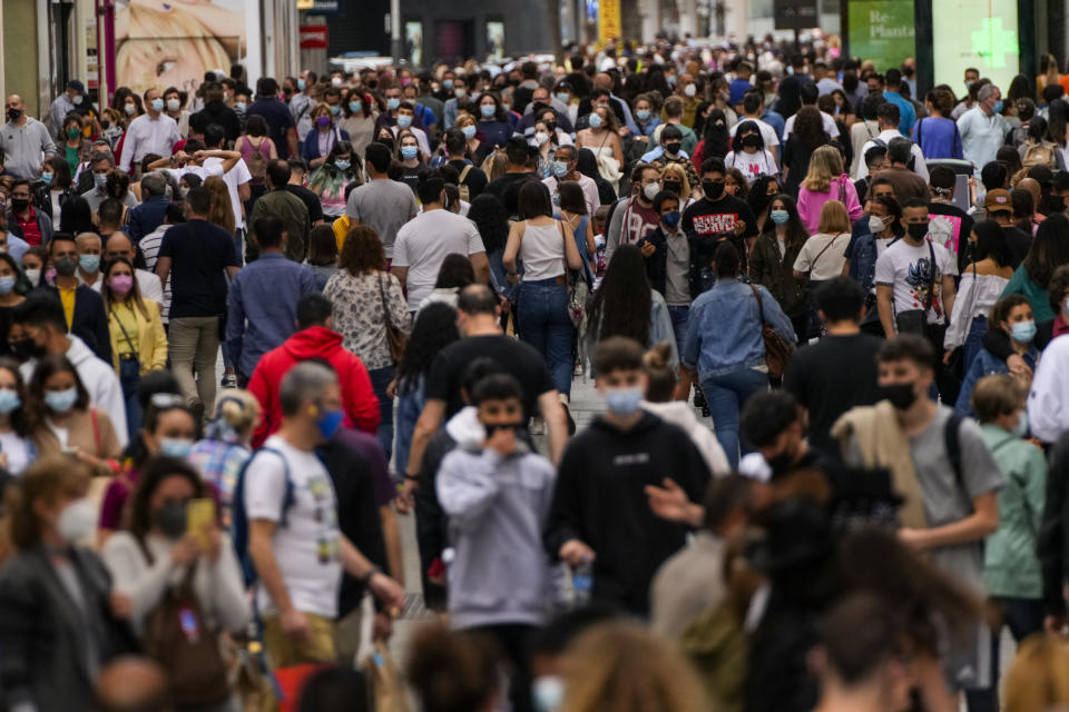 FILE - In this June 5, 2021, file photo, people wearing face masks to protect against the spread of coronavirus, walk along a commercial street in downtown Madrid, Spain. Countries across Europe are scrambling to accelerate coronavirus vaccinations to outpace the spread of the delta variant in a high-stakes race to prevent hospital wards from filling up again with patients fighting for their lives. (AP Photo/Manu Fernandez, File)