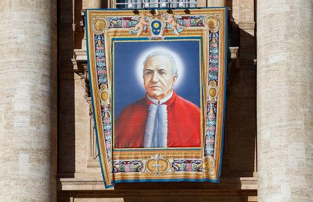 The tapestry of Alfonso Maria Fusco, one of the seven new saints, hangs from Saint Peter's Basilica before the start of a canonization mass led by Pope Francis at the Vatican October 16, 2016. REUTERS/Tony Gentile
