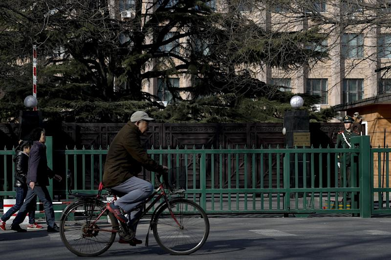 Pedestrians pass by a Chinese paramilitary policeman standing guard outside the North Korea Embassy in Beijing, Tuesday, Feb. 28, 2017. A top North Korean diplomat is visiting Beijing in the wake of China's ban on coal imports from its neighbor and the assassination of North Korean leader Kim Jong Un's older half-brother in Malaysia. (AP Photo/Andy Wong)