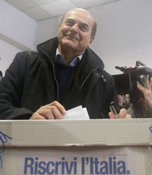 "Pier Luigi Bersani, leader of the center-left Democratic Party, casts his vote during a primary runoff, in Piacenza, Italy, Sunday, Dec. 2, 2012. Italians are choosing a center-left candidate for premier for elections early next year, an important primary runoff given the main party is ahead in the polls against a center-right camp in utter chaos over whether Silvio Berlusconi will run again. Sunday's runoff pits veteran center-left leader Pier Luigi Bersani, 61, against the 37-year-old mayor of Florence, Matteo Renzi, not shown, who has campaigned on an Obama-style ""Let's change Italy now"" mantra. Foreground Italian reads: ""Rewrite Italy""(AP Photo/Antonio Calanni)"