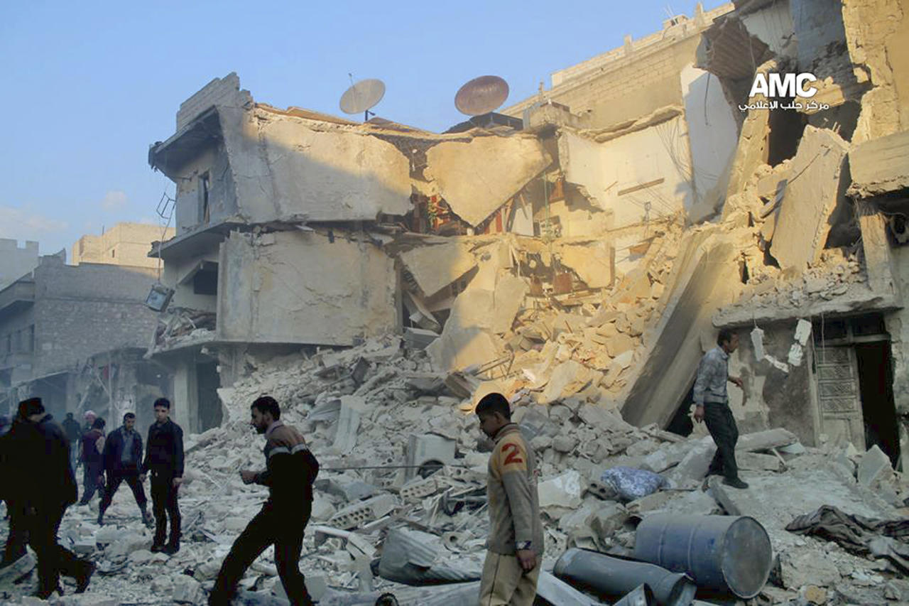 In this Sunday, Dec. 15, 2013 citizen journalism image provided by Aleppo Media Center, AMC, which has been authenticated based on its contents and other AP reporting, Syrians inspect the rubble of damaged buildings following a Syrian government airstrike in Aleppo, Syria. The Britain based Syrian Observatory for Human Rights said Monday that dozens of children were among scores killed in airstrikes on several opposition areas a day earlier. (AP Photo/Aleppo Media Center AMC)