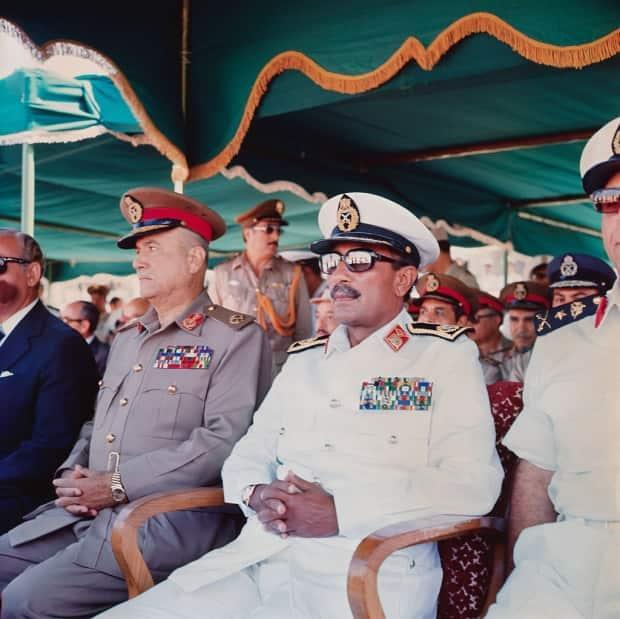 Egyptian President Anwar Sadat, wearing dark glasses and naval uniform, attends the reopening ceremony for the canal on June 5, 1975.
