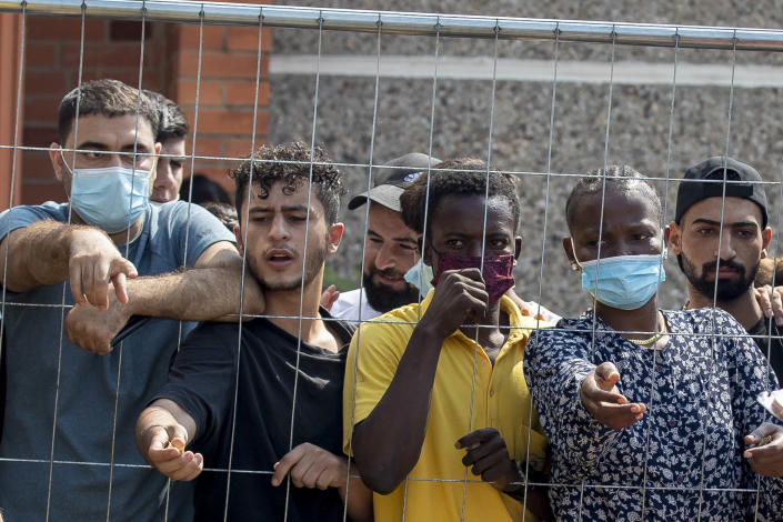 Migrants wait to buy some things standing behind the fence at the refugee camp in the village of Verebiejai, some 145km (99,1 miles) south from Vilnius, Lithuania, Sunday, July 11, 2021. Migrants at the school in the village of Verebiejai, about 140 kilometers (87 miles) from Vilnius, haven't been allowed to leave the premises and are under close police surveillance. Some have tested positive for COVID-19 and have been isolated in the building. (AP Photo/Mindaugas Kulbis)