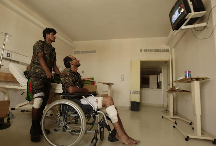 Wounded policemen are seen at a hospital following a suicide bomb attack at parade square in Sanaa, Yemen, Monday, May 21, 2012. Officials say Monday's bombing near Sanaa's presidential palace is one of the deadliest attacks in the city in months. (AP Photo/Hani Mohammed)