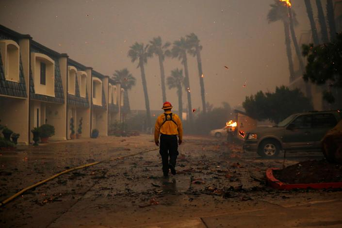 <p>A firefighter walks through an apartment complex as the Woolsey Fire burns in Malibu, Calif., Nov. 9, 2018. (Photo: Eric Thayer/Reuters) </p>