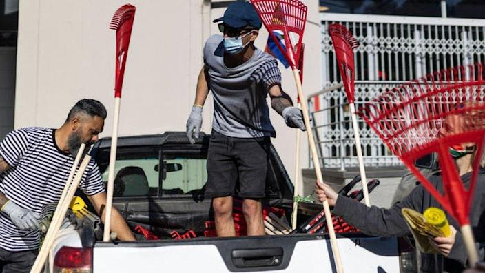Volunteers collect rakes and other cleaning material during a cleanup operation organised by the Grace Family Church in Durban on 18 July 2021