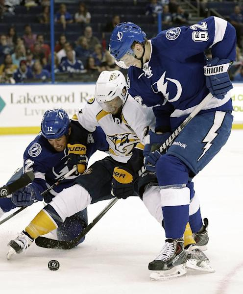 Tampa Bay Lightning defenseman Andrej Sustr (62) and left wing Ryan Malone (12) team up to take down Nashville Predators center Matt Cullen (7) during the first period of an NHL preseason hockey game, Thursday, Sept. 19, 2013, in Tampa, Fla. (AP Photo/Chris O'Meara)