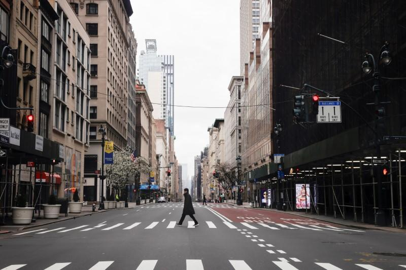 A man crosses a nearly empty 5th Avenue in midtown Manhattan during the outbreak of the coronavirus disease (COVID-19) in New York